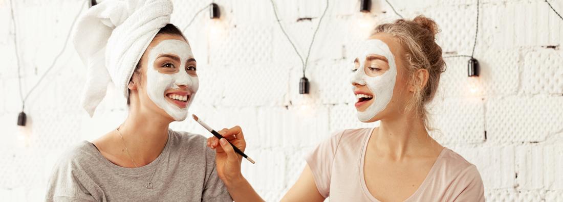 Två unga kvinnor med ansiktsmasker från LYKO som skrattar