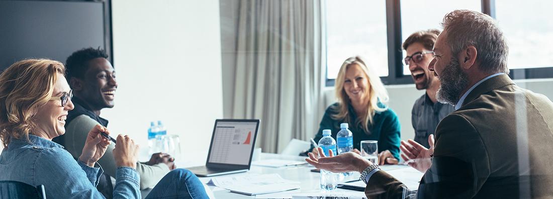 Kollegor i affärsmöte som skrattandes disukterar expansionsplaner och extern finansiering