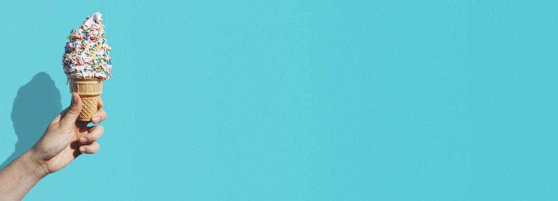 Hand som håller mjukglass med strössel under sommarsäsongen mot turkos bakgrund
