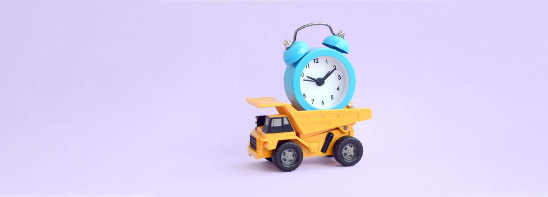 Gul hjullastare med en blå och vit tidsvisare på flaket mot lila bakgrund