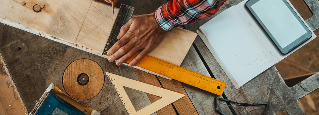 Man i rutig skjorta i verkstad mäter ut och markerar på en bräda med hjälp av vinkelhake från Verktygsboden
