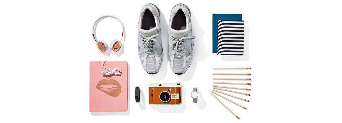 Olika produkter som hörlurar, ett par skor, kamera, klocka, pulsmätare, anteckningsblock och blyertspennor mot vit bakgrund