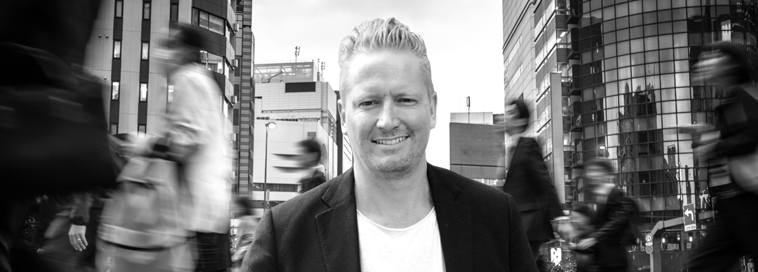 Jonas Carlstrom på Star Republic iklädd svart kavaj och vit t-shirt på gata i storstad